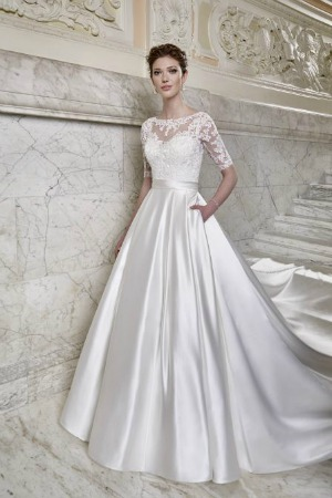 c19b2e510676e4 A beaded lace and satin ballgown style wedding dress featuring a sweetheart  neckline with sheer illusion lace overlay, wide satin belt, half sleeves  and ...